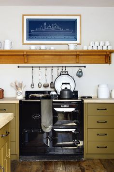 A black Aga with units in green wood, white walls & wooden shelves. Aga Kitchen, Kitchen Units, Open Plan Kitchen, Kitchen Cabinets, Kitchen Ideas, Olive Kitchen, Kitchen Country, Green Cabinets, Cupboards