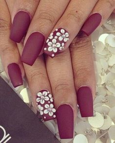 Floral themed maroon nail art design. The flowers are asses as embellishments on top and they are in white color. The white becomes a perfect contrast to the matte maroon nail polish below.