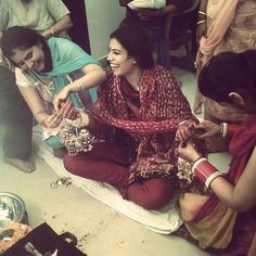 Indian wedding rituals at a Punjabi wedding. The sisters and friends of the bride tie the kaleeras (danglers) on the chudas (red and white bangles) worn by the bride on the day of the wedding.