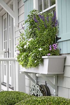 Window boxes set on white-painted wood brackets add to the cottage aesthetic, as do the aqua-painted board-and-batten shutters. | Photo: Laura Moss
