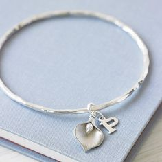 A gorgeous, personalised solid silver bangle with a delicate matte silver plated lily pendant and sterling silver initial charm.Charm initials: A-Z.This pretty, softly hammered solid silver bangle would make a lovely gift for someone special in your life. The addition of the sterling silver initial charm makes this bangle personalised and unique. Each bangle arrives beautifully packaged in a pretty chiffon bag wrapped in aqua tissue, an eco-friendly pillow box and chiffon ribbon with my…