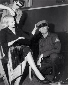 Check out this image from TCM.   Medium BTS shot of director Alfred Hitchcock with women at stand.
