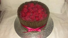Dark chocolate cigarello cake topped with fresh raspberries, trimmed with ruby satin ribbon. Chocolate sponge with chocolate buttercream frosting inside.