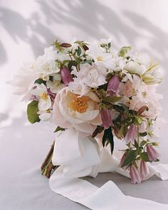 Sharon's Bouquet     Sharon's hand-tied cascade bouquet mixes pale-pink peonies, sweet peas, azaleas, white mock orange, bell-shaped campanula, clematis, and garden roses; it's secured with a sash of vintage kimono silk.
