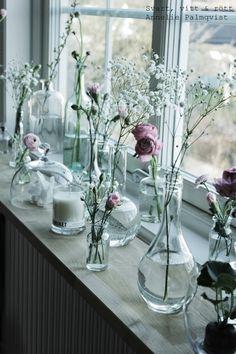 la bruket doftljus, citrongräs ljus, arrangemang i fönster, prydnad i fönstret, ordna glasflaskor från loppis på fönsterbänken och ställ i snittblommor, rosa och vitt, inspiration, inredning, arbetshörna, ljusinsläpp, stort fönster, tips