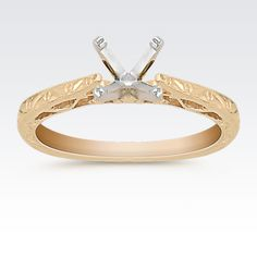 This classic cathedral solitaire design features a lovely swirl design.  Crafted in quality 14 karat yellow gold, this ring simply awaits the center diamond of your choice.