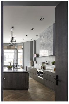 Fan hidden behind marble stale. Grey scale, dark woof kitchen. Modern, slightly industrial