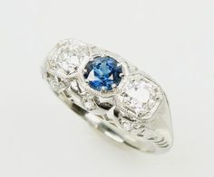 Truly lovely. This perfect 3 stone Edwardian Platinum Engagement ring is set with a .71 point blue sapphire in the center and flanked by 2 old mine cut diamonds. The sides of the ring are decorated wi