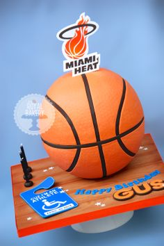 "Miami Heat Basketball Cake - Basketball cake for Gus, who loves Miami Heat. The logo is an edible image. The bottom of the basketball is an 8"" hollow styro hemisphere, the top half is cake."