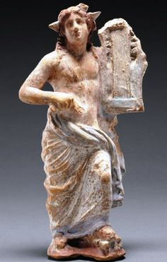 Apollo stands holding His kithara - stringed harplike instrument, terracotta statue, found South Italy, circa 300 B.C. at the Getty Museum