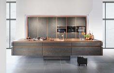"""Hinter den grifflosen Türen aus mattem Stein blitzen die kupfernen Korpuskanten des Küchensystems """"Horizon"""" hervor. Der Glanz lässt den…"""