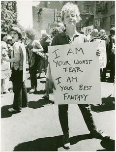 """A woman holding a poster that says, """"I am your worst fear I am your best fantasy,"""" at the Christopher Street Gay Liberation Day parade in 1970."""