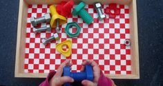 Tray Activities: Matching multicolored nuts and bolts.