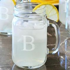"""Set of four monogrammed glass drinking jars. Made in the USA.Product: Set of 4 drinking jarsConstruction Material: GlassColor: ClearFeatures:  Made in the USAFashionable handle Dimensions: 5.25"""" H x 2.63"""" Diameter eachNote:  May be engraved with a single initial at no additional cost"""