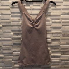 Lululemon tank with built in bra Excellent condition light gray/pink lulu top. Crisscross straps, scoop band with a pink band in the back. Dark ribbed fabric on the sides for a sexy silhouette. Very flattering all the way around. Never worn to workout lululemon athletica Tops Tank Tops