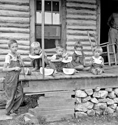 Millworker's children eating watermelon on porch of rented house. Six miles north of Roxboro, Person County, North Carolina, July 1939. Dorthea Lange photo