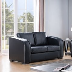 Modernize your living room with this comfy loveseat. This loveseat features firm seats with pocket coil cushions and piping design. The handsome black finish allows for a sleek modern feel.