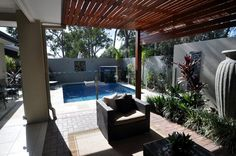 Outdoor room with an inground pool by Evans and Evans Pools