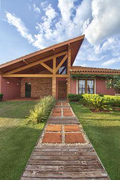 A composição com cruzetas, pedriscos e arenito vermelho marca a entrada principal na fachada. O paisagismo é assinado por Luiz Felipe Rudge Leite