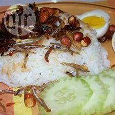 Malaysisches Nasi Lemak / Kokosreis auf malaysische Art mit einer scharfen Sardellensoße, frittierten Sardellen, frittierten Erdnüssen, Gurke, Tomate und hartgekochtem Ei. @ de.allrecipes.com