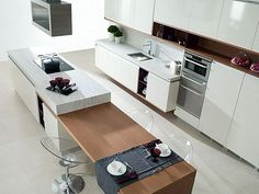 Contemporary kitchen with combination island bench with stools in table setting