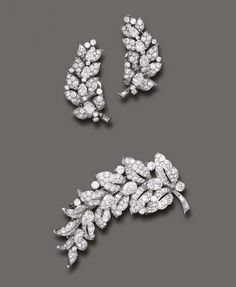 AN ELEGANT SET OF DIAMOND JEWELRY, BY BULGARI   Comprising a brooch, designed as a pierced pavé-set diamond leaf, enhanced by pear-shaped diamonds and a baguette-cut diamond stem; and a pair of ear clips en suite, mounted in platinum  Signed Bulgari