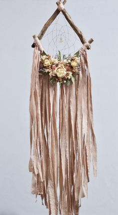 Handmade 10 wide dream catcher with dried flower adornments in shades of blush, ivory and pale peach. The total length from the top of the hanger to the bottom of the fringe is just over 30. This delicate blush pink is so sweet and feminine, but muted enough to not be overly girly- perfect for
