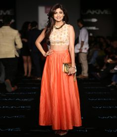A fetching princeton orange, ankle length silk skirt paired with a beige crepe crop top with aztec print and badla work butis. The enchanting Shilpa Shetty Kundra  wore this ensemble to Lakme Fashion Week 2014.