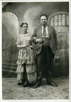 """Frida y Diego le jour de leur mariage. Coyoacán,21 août 1929: """"D'un côté le monstre énorme, rabelaisien, ogre vorace; de l' autre la frêle """"danseuse"""", si menue, si ardente, si fragile. Frida a emprunté ses vêtements à une domestique indienne. Ce long vêtement somptueux, cache autant les marques extérieures de sa souffrance physique que celles de sa souffrance psychique; elle se dote d'une nouvelle identité, avec une ferveur """"égale à celle d'une novice qui prend le voile""""( Erika Billeter)"""