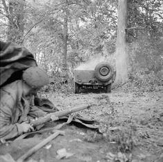 A paratrooper takes cover as a jeep burns during a German mortar attack on 1st Airborne Division's HQ at the Hartenstein Hotel in Oosterbeek, near Arnhem, 24 September 1944. (IWM)