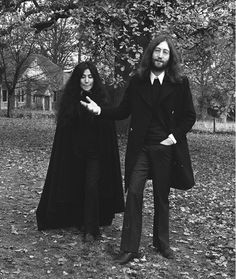 Yoko Ono wears a long black cape with separates, John Lennon wears a button-down shirt, sweater, coat, and flare pants