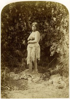 Photograph (black and white); portrait of Ka-ni, a Paiute woman, standing on an animal skin, wearing a fibre loin covering; trees are a behind her; Nevada, United States of America.  Albumen print