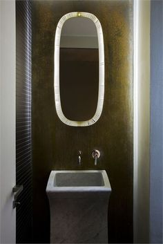 lighted mirror. and perfect wall treatment and basin.