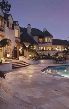 Huge mansion with pool and lit up with a bunch of lights.