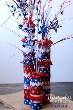 I love celebrating the of July, and I especially enjoy decorating my house with red, white, and blue in anticipation of the special day, so today I'm excited to share how to make a cute and festive ribbon Firecracker Table Display! 4th July Crafts, Fourth Of July Decor, 4th Of July Celebration, 4th Of July Decorations, Party Table Decorations, Patriotic Crafts, 4th Of July Party, Party Centerpieces, July 4th