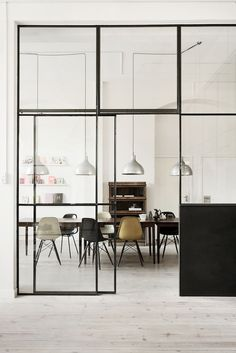 A metal framed glass wall separates the dining area in this modern with whitewashed hardwood floors.