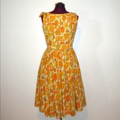 """Vintage Summer Dress Pleated Boat Neck S M Adorable tiki style mid length fit and flare dress in lined nylon mid length with an adorable boat neckline and pleated full skirt.  It's perfect for spring with a floral and leaf print in gold, yellow, orange, green and white.  Zips up the back with a metal zipper and a hook at the top. good condition with one spot 2"""" long on the waist line seam that has been restitched Material: Lined nylon Maker: Maggi Stover Era: 50's 60's Size: S M  Bust-  36""""…"""