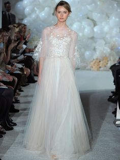 Mira Zwillinger Spring 2018 peach tulle full skirt gown with appliquéd and beaded Chantilly bodice with feather accents, and tulle coat with embroidery and feather trim