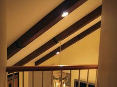 Steve Watson helps a couple install faux ceiling beams to add a rustic touch to their living room.