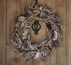 WINTER WOODS WREATH ♦ Real pinecones & faux pine branches are sprinkled w/ frosty layers of glitter on this snowy indoor/outdoor wreath.