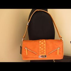 NWT XOXO orange purse. NWT. Never worn. Like suede material. Orange color. It has an almost unnoticeable dark discolor in the small part of the inside above the zippered pocket as shown in the last pic. Other than that  is in excellent condition. xoxo Bags