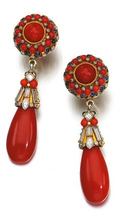 Elmar Seidler - A pair of Art Deco coral, sapphire and diamond pendent earrings, 1930s. Each surmount set with polished coral, sapphire cabochons, brilliant- and single-cut diamonds, suspending a coral drop, the surmount set with similar stones, including baguette and square diamonds, unsigned, hook fittings. #Seidler #ArtDeco #earrings