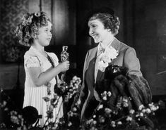 1935: Shirley Temple, recipient of a special miniature Juvenile Oscar, chats to Claudette Colbert, winner of Best Actress for It Happened One Night