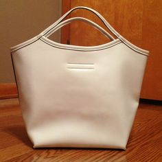 Mondani TOTE White cute tote by: Mondani:: used twice as seen in picture 3 it had a slight blk mark:: inside of the tote is an Olive green it also has a velcro instead of a zipper to close the tote:: cute hole design in front of purse Mondani Bags Totes