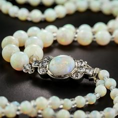 Antique double-strand opal bead necklace, circa late 19th century. Double-strand opal bead necklace culminating in a decorative opal and diamond clasp, designed to be worn in front. Graduating beads display a shimmering color profile of pastel green and blue with flashes of yellow and orange.