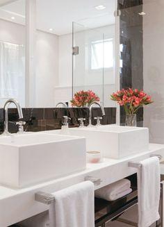Presos à bancada de mármore pigués, os toalheiros, com 35 cm de largura, são providenciais em um banheiro onde o espelho, de 1,80 x 1,40 m, ocupa boa parte da parede. As cubas de apoio medem 41 x 41 x 15,5 cm.