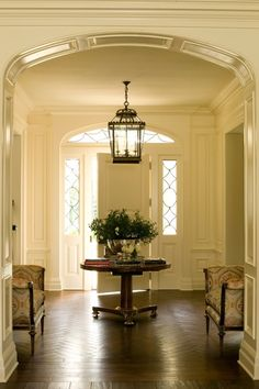 The paneled entry hall features an oversized front door with leaded glass sidelights and traditionally detailed arched transom. Herringbone walnut flooring helps to unite two strong cross axes of the space.