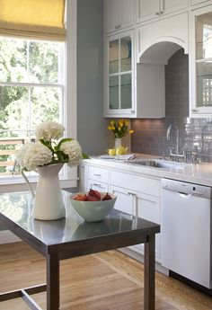 Fabulous kitchen color scheme -- white, silver / gray on the tile and work table, with a hint of yellow and green.