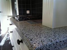 """Hier is gekozen voor een nostalgische """"look"""". Een witte keuken met zwarte knoppen en een prachtig terrazzo/granito aanrecht.  Het aanrecht is op maat gemaakt zodat het perfect past met de schouw en de kookplaat. www.terrazzoruesink.nl"""