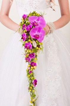 A slim cascading bouquet of purple phalaenopsis orchids with some green berries.